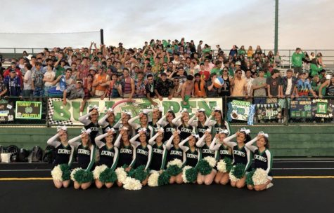 Notre Dame Cheerleaders with the Notre Dame student section at a football game.