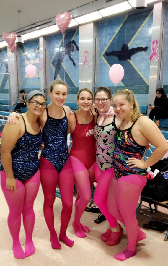 Swim team shows their support for breast cancer awareness month.