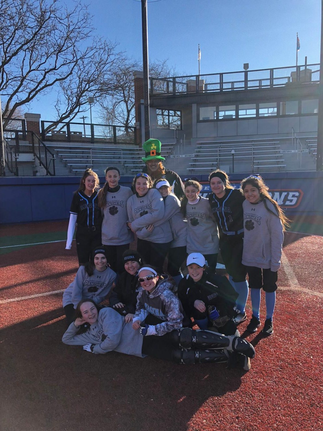 Varsity Softball celebrates their St. Patrick's day victory after their first double header of the season